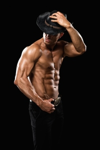 Portrait of young shirtless male athlete and fashion model wearing cowboy hat.